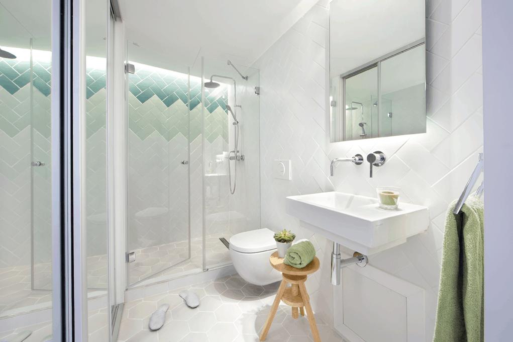 Cuarto de baño con azulejos blancos y sanitarios ...